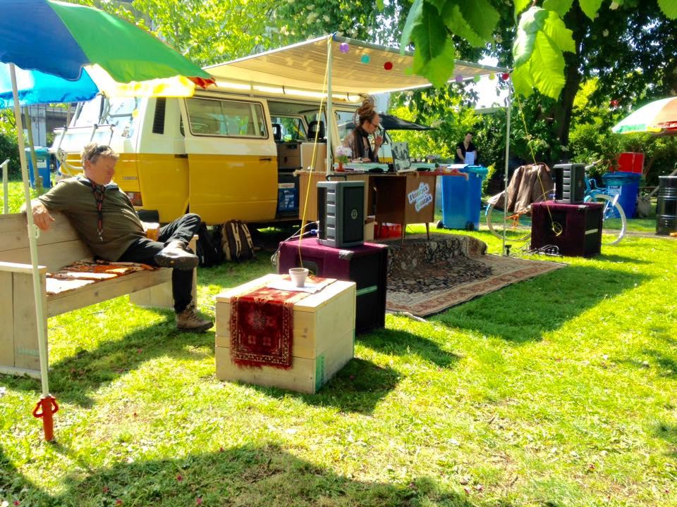 Het campingbusje met meubels er omheen in het zonnetje