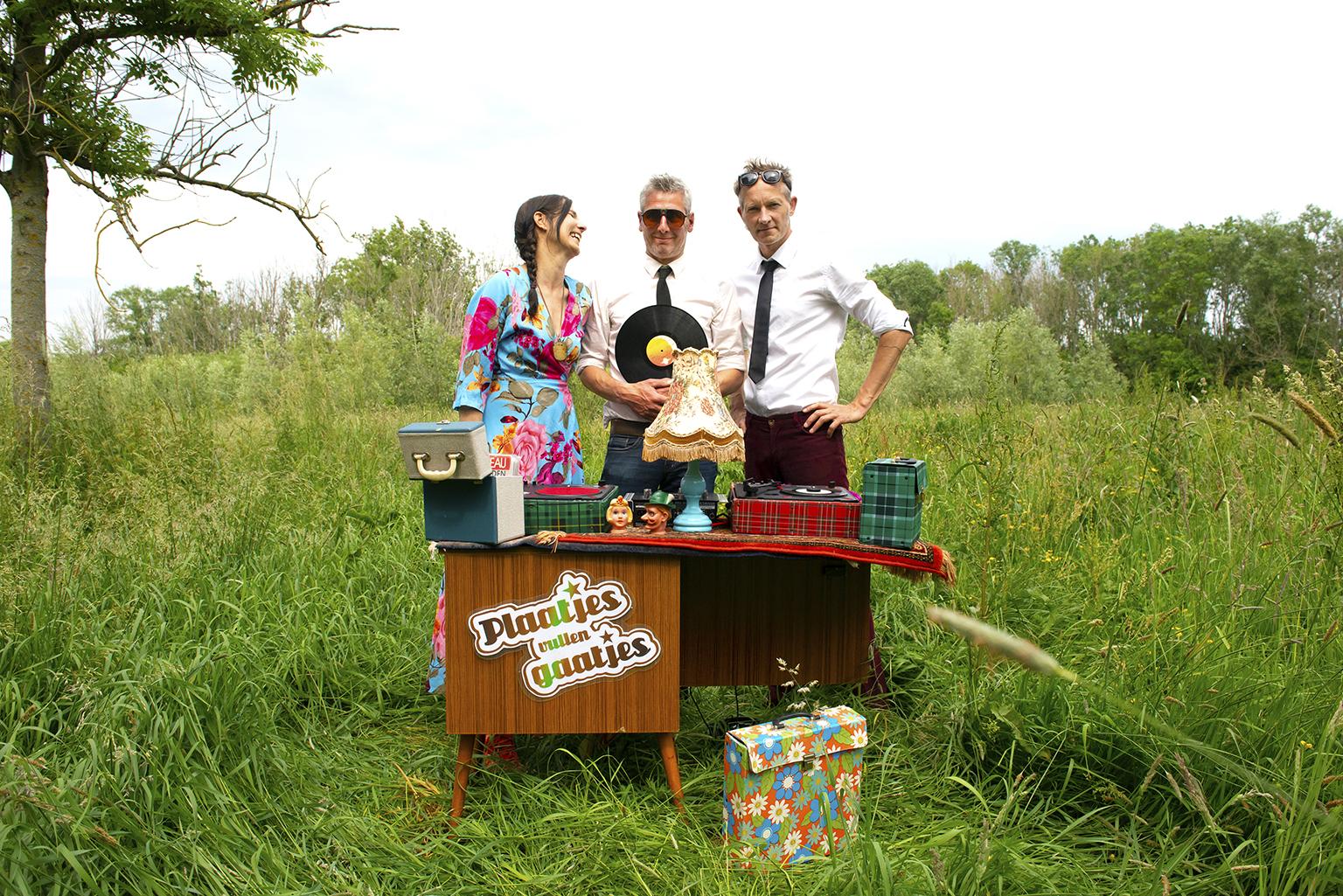 Marieke, Pieter en Erik met een oud kastje en platenspeler in een weiland
